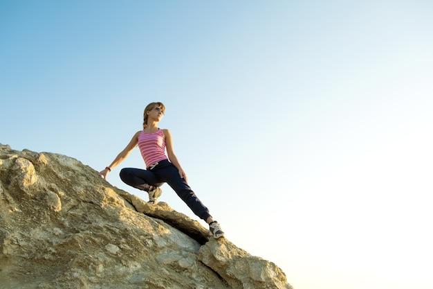Woman hiker climbing steep big rock on a sunny day
