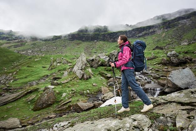 Женщина турист, наслаждаясь видом во время похода с ее рюкзаком в горах