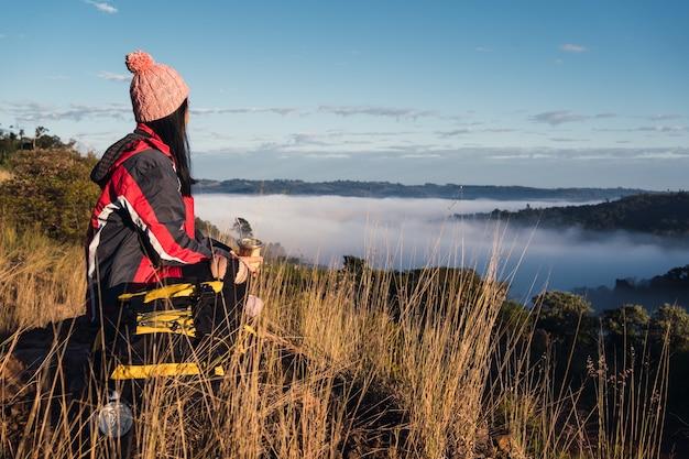 A woman hiker enjoys a break on the mountain top.