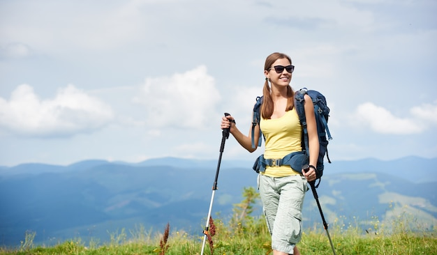 Woman hiker hiking on grassy hill, wearing backpack, using trekking sticks in the mountains