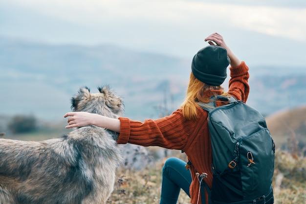 여성 등산객은 자연 풍경 산 여행에 개를 안 아