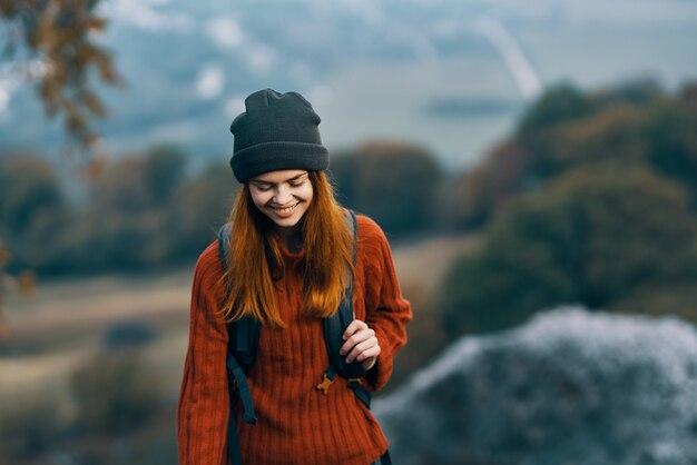 山の風景の休暇の冒険で帽子をかぶった女性ハイカー