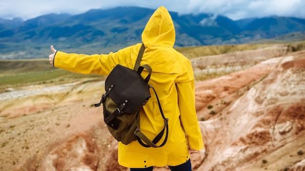 Путешественник женщина в желтом плаще с рюкзаком на фоне гор показывает палец вверх.