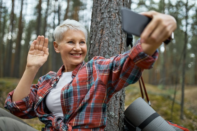 Женщина-путешественница в спортивной одежде, делающая селфи с помощью смартфона