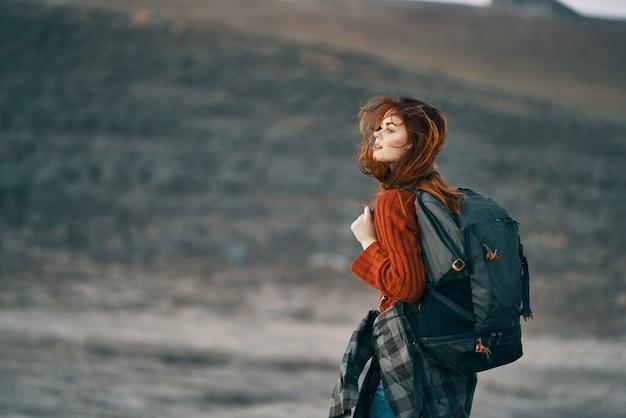 山の女性ハイカーはバックパックの風景と一緒に旅行します。高品質の写真