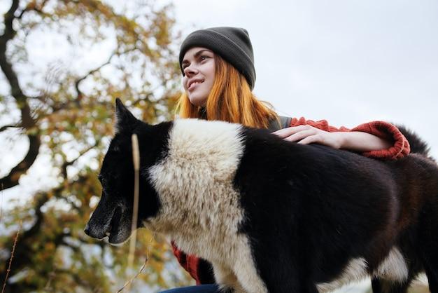 犬の休息の楽しい友情と自然の中で女性ハイカー。高品質の写真