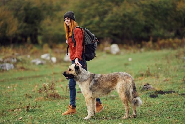 Путешественник женщина в поле, играя с собакой путешествия на природе