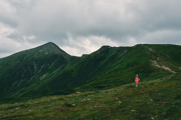 Путешественник женщина в горах, покрытых травой. горный пейзаж в тумане и пасмурную погоду. активный образ жизни, покорение вершин, свобода.