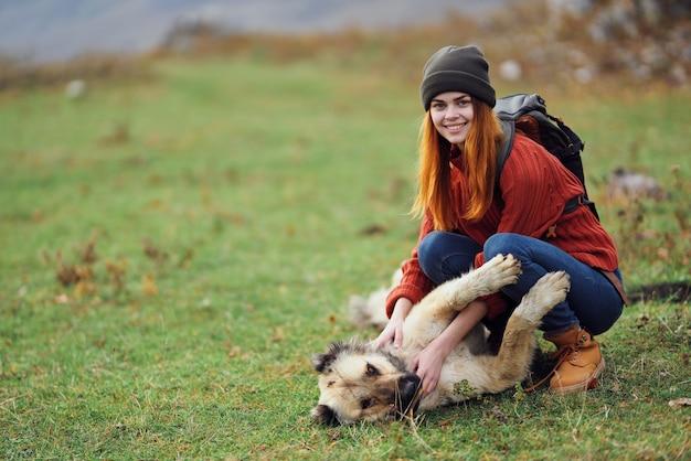山の女性ハイカーは、犬の隣の芝生の上に横たわって楽しんでいます
