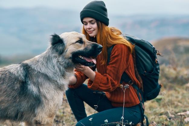 犬の隣の山の女性ハイカー