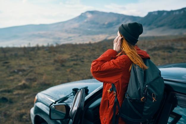 後ろにバックパックを背負って車の近くの自然の山で女性ハイカー。高品質の写真