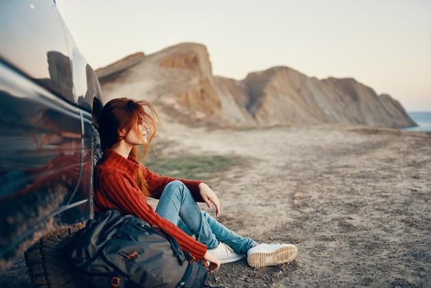 자연에 산에서 여성 등산객은 배경 하늘 도로에서 자동차와 산 근처에 앉아