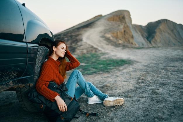 Путешественница женщина в горах на природе сидит возле машины и горы в пейзаж дороги неба