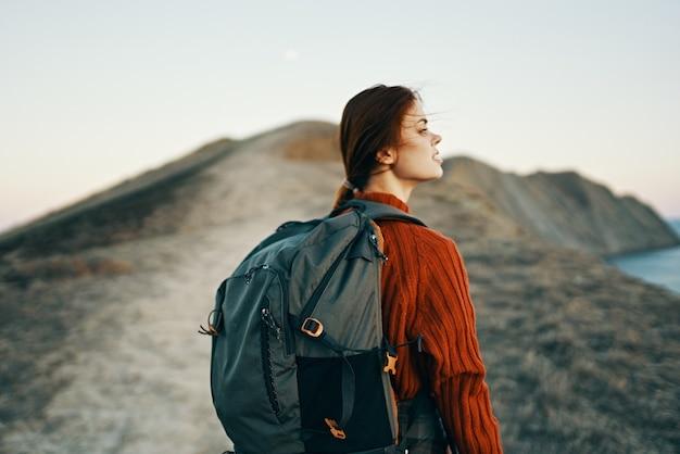山のアウトドアアドベンチャーバックパックトレイルモデルの女性ハイカー