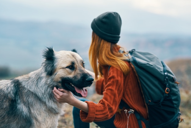 犬の旅行の隣の屋外の山で女性ハイカー