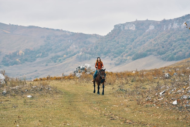 馬の冒険のライフスタイルに乗って山の女性ハイカー