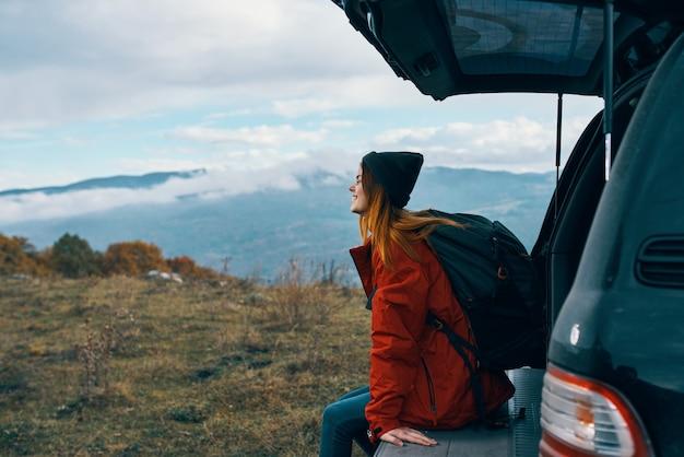 차 근처 산에서 가을에 쉬고 따뜻한 옷을 입은 여성 등산객