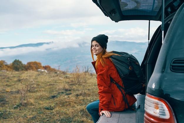 車の近くの山で秋に休む暖かい服を着た女性ハイカー