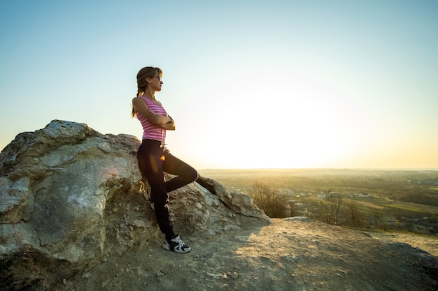 暖かい夏の日を楽しんでいる大きな岩に寄りかかっている女性ハイカー。自然の中でスポーツ活動中に休んでいる若い女性登山家。自然の概念のアクティブなレクリエーション。