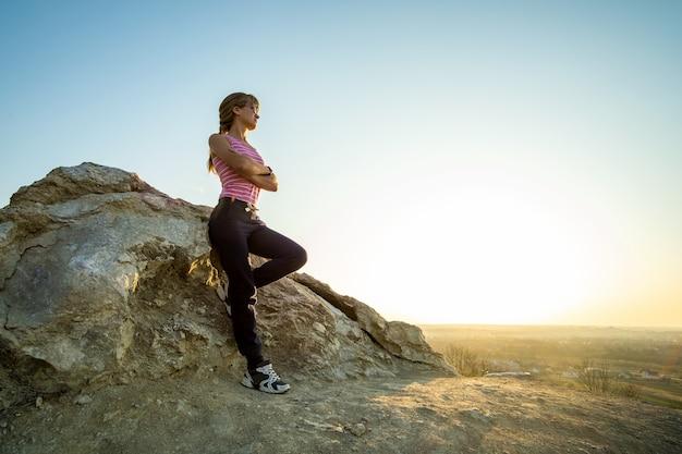 따뜻한 여름날을 즐기는 큰 바위에 기대어 여자 등산객. 자연 속에서 스포츠 활동을 하는 동안 쉬고 있는 젊은 여성 산악인. 자연 개념의 활동적인 레크리에이션.