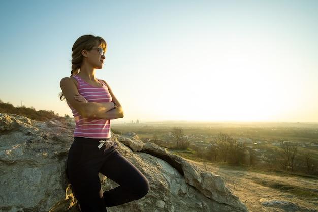 暖かい夏の日を楽しんでいる大きな岩にもたれて女性ハイカー。自然の中のスポーツ活動中に休んで若い女性登山家。