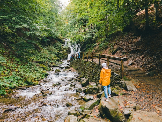 Путешественник женщина смотрит на пространство копии карпатского водопада