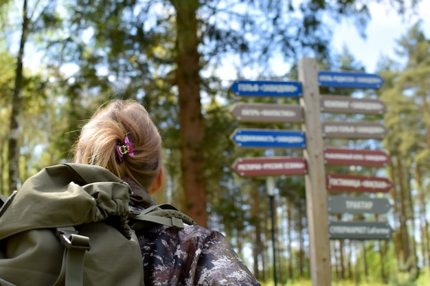 Woman hiker looking at road wooden signs in the forest looking for directions