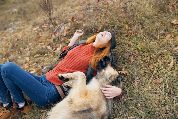Woman hiker lying on the grass next to the dog friendship fun games