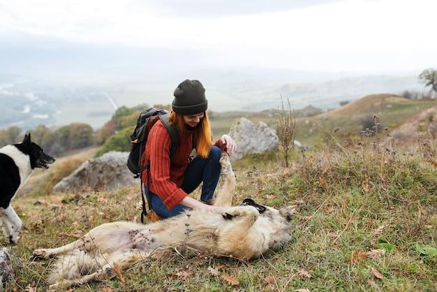 犬の友情の楽しいゲームの横にある芝生の上に横たわる女性ハイカー
