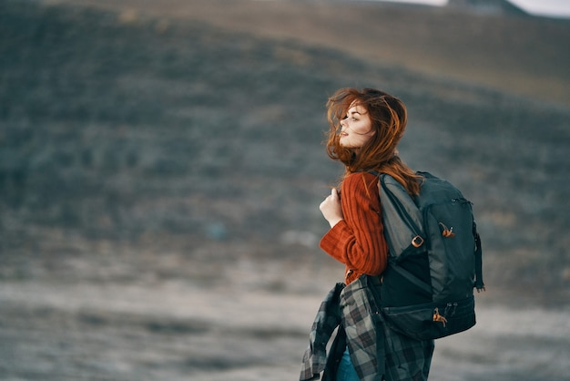 Woman hiker in mountains travel with backpack landscape. high quality photo
