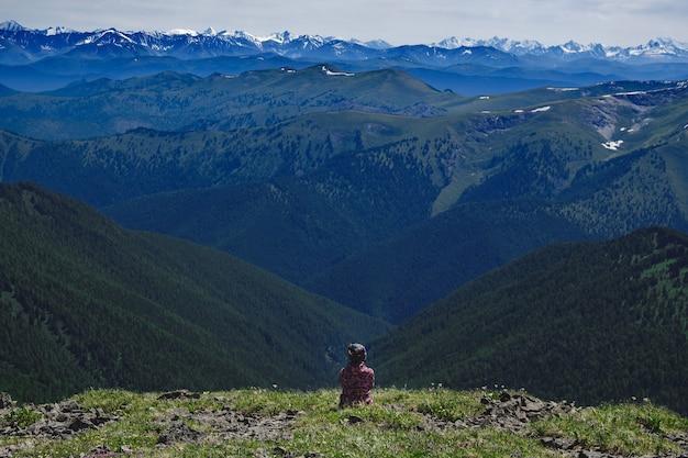 Путешественница на вершине горы, наслаждаясь видом на горные хребты в улаганском районе республики алтай, россия