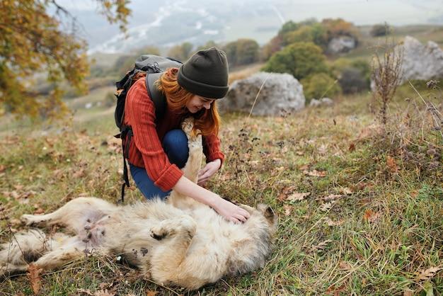 Путешественник женщина на открытом воздухе играет с собакой весело дружбы