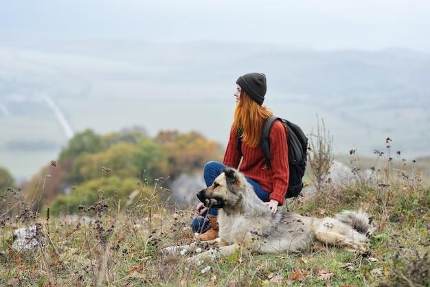 Путешественник женщина играет с собакой на открытом воздухе горы свежий воздух природа