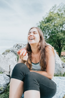 Woman hiker resting and eating an apple sitting while laughing and smiling, copy space, hiking and freedom concept