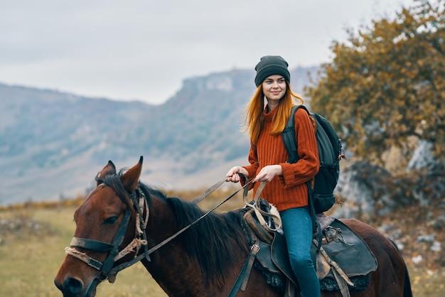 女性ハイカーに乗る馬の山は新鮮な空気を旅行します