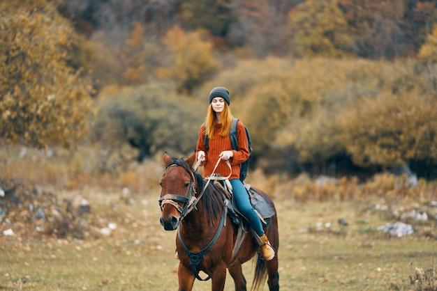 女性ハイカーが野原の山の自然の風景で馬に乗る