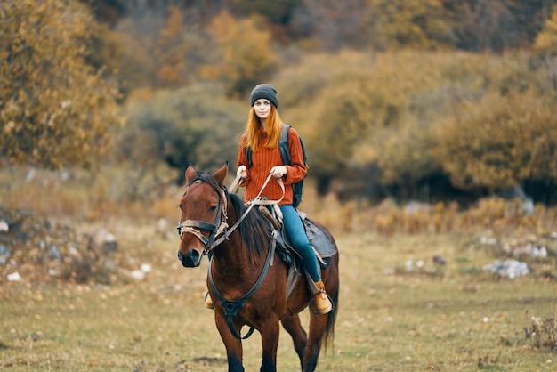 女性ハイカーは、フィールド山の自然の風景の中で馬に乗る