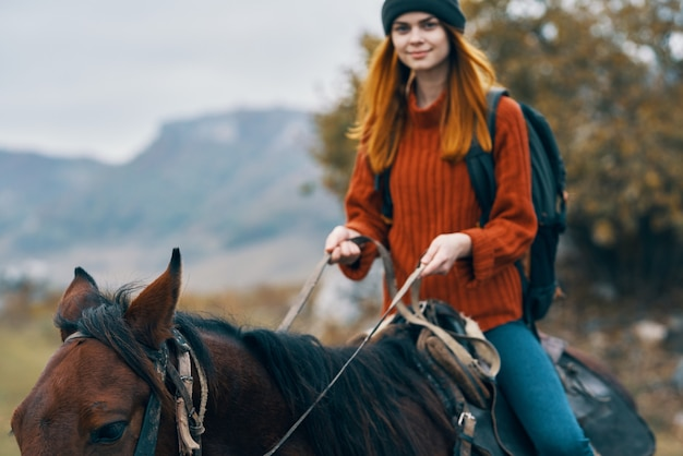 山で馬に乗る女性ハイカーは新鮮な空気の楽しみを旅行します。高品質の写真