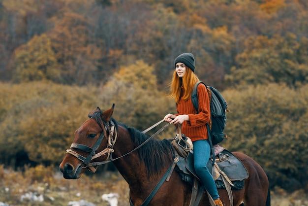 山で馬に乗る女性ハイカーが新鮮な空の旅を歩く