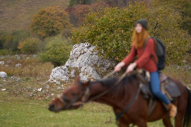 自然の山の冒険に馬に乗る女性ハイカー