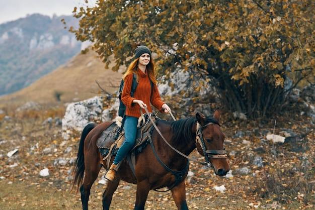 馬の山の風景旅行の冒険に乗る女性ハイカー
