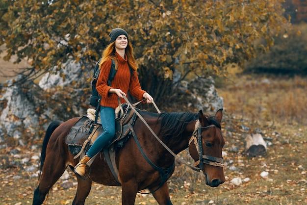 馬の山の風景旅行の冒険に乗っている女性ハイカー