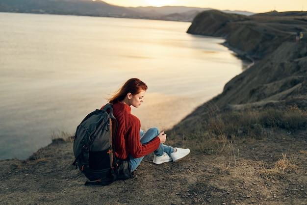 日没時に海の近くの山の地面に座っている女性ハイカー