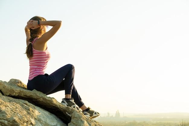 暖かい夏の日を楽しんでいる急な大きな岩の上に座っている女性ハイカー。自然の中でスポーツ活動中に休んでいる若い女性登山家。自然の概念のアクティブなレクリエーション。