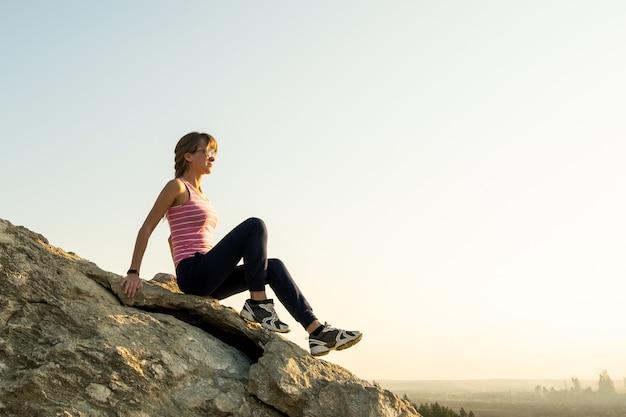 여성 등산객은 따뜻한 여름날을 즐기는 가파른 큰 바위에 앉아 있습니다. 자연 속에서 스포츠 활동을 하는 동안 쉬고 있는 젊은 여성 산악인. 자연 개념의 활동적인 레크리에이션.