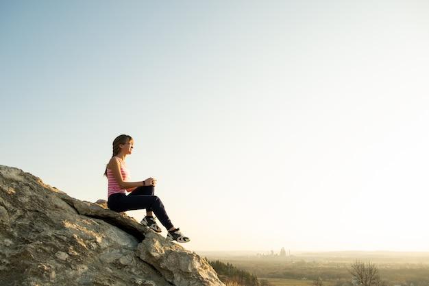 暖かい夏の日を楽しんでいる急な大きな岩の上に座っている女性ハイカー。自然の中のスポーツ活動中に休んで若い女性登山家。