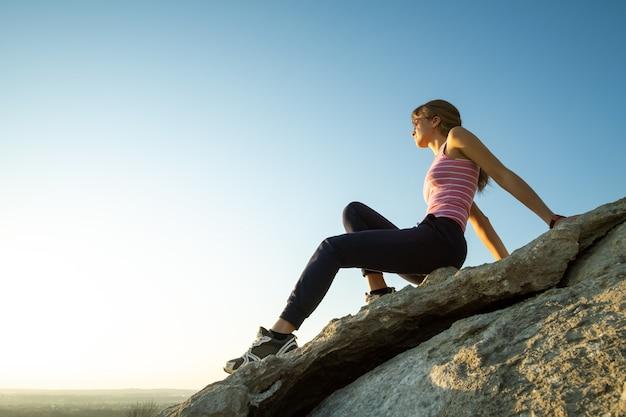 暖かい夏の日を楽しんで急な大きな岩の上に座っている女性ハイカー