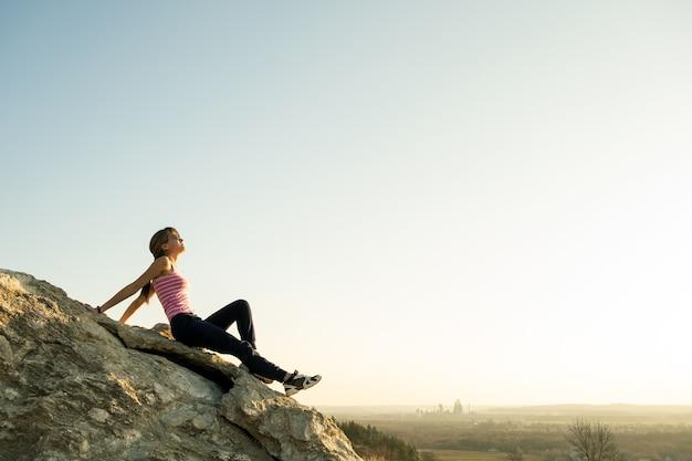 暖かい夏の日を楽しんでいる急な大きな岩の上に座っている女性ハイカー。