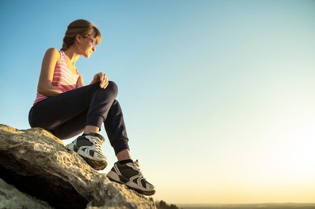 여성 등산객은 따뜻한 여름날을 즐기는 가파른 큰 바위에 앉아 있습니다.