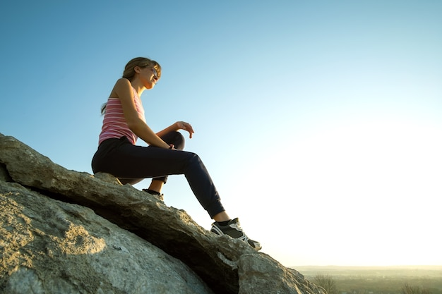 Woman hiker sitting on a steep big rock enjoying warm summer day. young female climber resting during sports activity in nature. active recreation in nature concept.